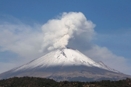 The snow-covered Popocatepetl volcano spews a cloud of steam high into the air.