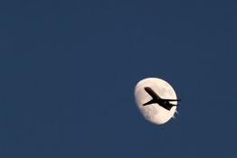 An airplane passes by the moon in its waxing gibbous phase in the sky over Hoboken, New Jersey.