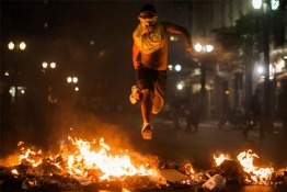 A demonstrator jumps over trash set afire during protests against poor public services, police violence and government corruption, in Sao Paulo.