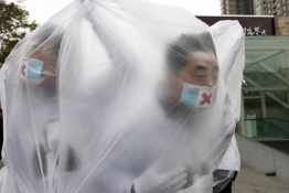College students wearing masks cover themselves with plastic bags as they participate in a performance art to raise awareness of air pollution, in Xi'an, Shaanxi province.