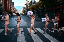 "Naked protesters walk through Bilbao carrying signs reading ""No To Social Services Cuts""."