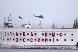 An attack helicopter, believed to Russian, flies over a Russian military base at the Crimean port of Sevastopol.