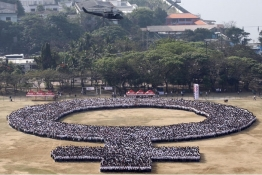 A military helicopter hovers over a female symbol formed by people, as part of celebrations for International Women's Day in Manila.