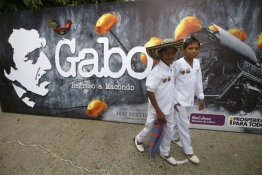 Residents walk next to a poster of Gabriel Garcia Marquez, before a symbolic public funeral in Aracataca.