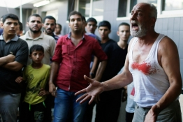 The father of a Palestinian boy reacts following his death at a hospital in Gaza City.