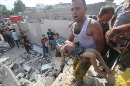 A Palestinian man carries the body of Palestinian girl, whom medics said was killed in an Israeli air strike.