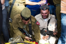 Israeli soldiers mourn next to the grave of Israeli soldier Daniel Kedmi during his funeral in Tel Aviv.