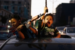 Palestinian children hold guns as they celebrate with others what they said was a victory over Israel, following a ceasefire in Gaza City.